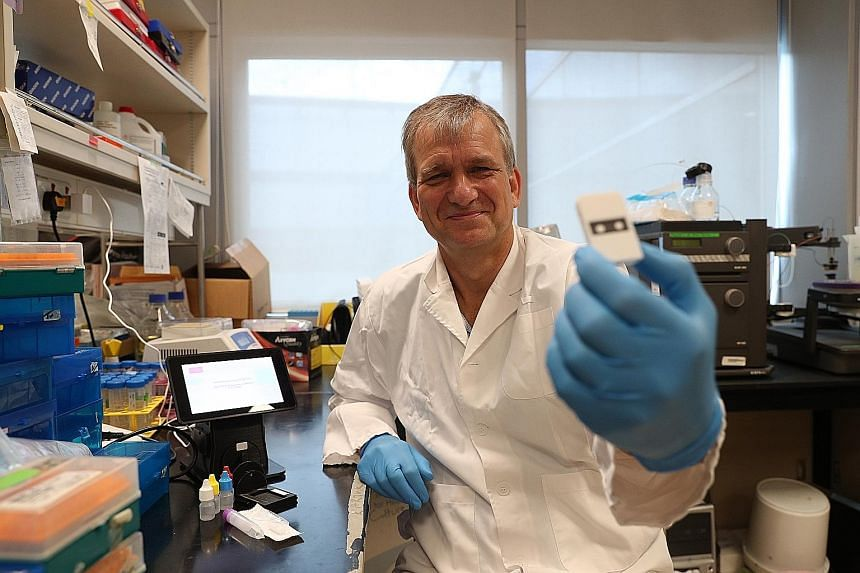 Professor Peter Preiser with the cellulose-based test he developed to detect proteins produced by the Sars-CoV-2 virus. ST PHOTO: TIMOTHY DAVID