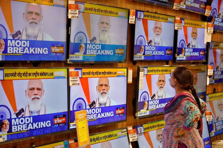 In a photo from Oct 20, 2020, a woman watches Indian Prime Minister Narendra Modi on TV screens inside a showroom in Ahmedabad.
