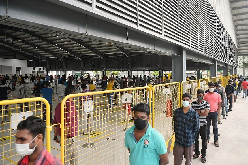 Migrant workers queueing to have a Covid-19 swab test at a regional screening centre in Sembawang in October. Second Minister for Manpower Tan See Leng said that by August, all migrant workers staying in dormitories had been tested at least once for