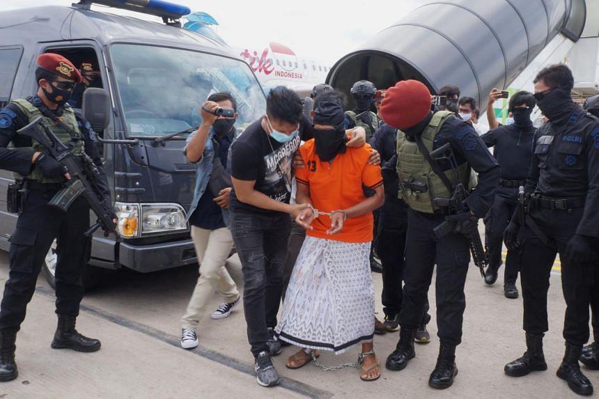 Police escort 57-year-old Zulkarnaen upon arrival at Jakarta's Soekarno-Hatta International Airport in Tangerang, on Dec 16, 2020.
