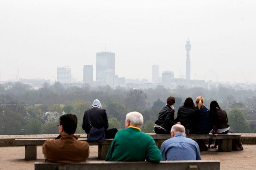 A 2014 photo shows London shrouded in pollution as people sit at the top of Primrose Hill.