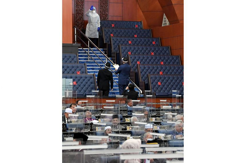 Malaysia's Human Resources Minister M. Saravanan wearing personal protective equipment during voting for the budget in Parliament yesterday. Datuk Seri Saravanan and two other MPs are under home quarantine for having been in close contact with a Covi