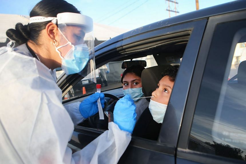 A health worker administers a nasal swab test at a drive-in Covid-19 testing site in El Paso, Texas.