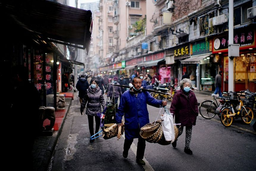 People walk at a street market in Wuhan, in China's Hubei province, on Dec 7, 2020.