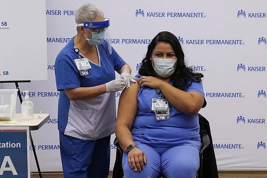 An ICU nurse receiving the Pfizer-BioNTech Covid-19 vaccine in Los Angeles, California, on Monday. Record coronavirus cases have left the county of 10 million people with fewer than 100 ICU beds available.