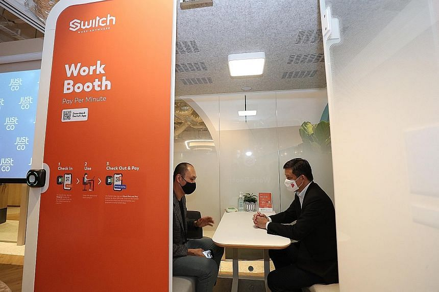 Trade and Industry Minister Chan Chun Sing and founder and chief executive of JustCo, Mr Kong Wan Sing, checking out the Switch work booth yesterday.