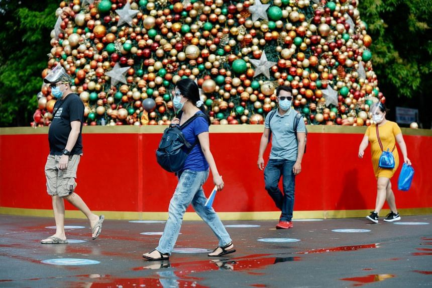 People wearing face masks walk past a Christmas tree in Manila, on Dec 17, 2020.