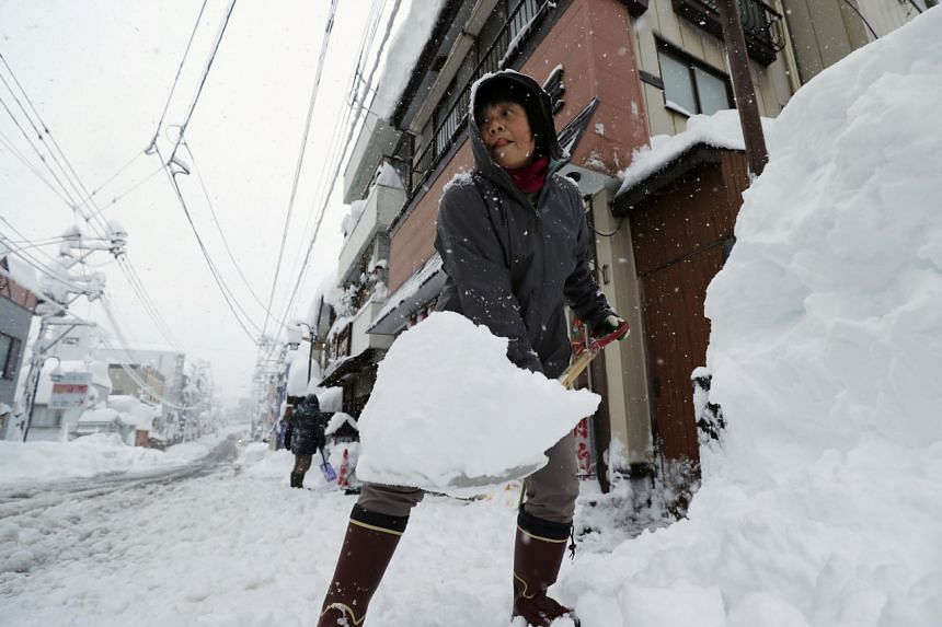 A woman removes snow on a street in Yuzawa, Japan, on Dec 17, 2020.