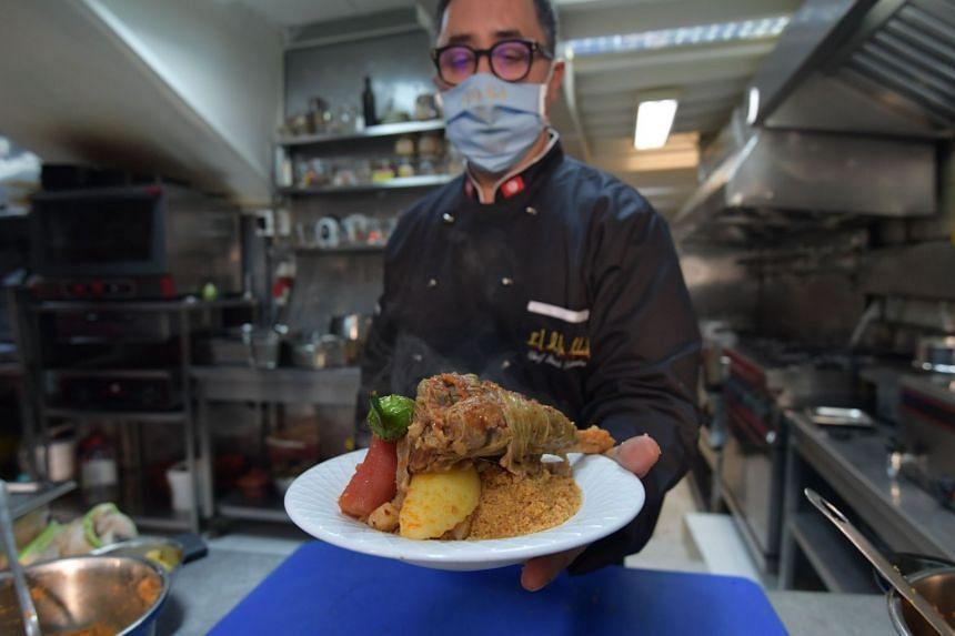 Tunisian chef Taieb Bouhadra presents a prepared traditional Tunisian lamb couscous dish at a restaurant in Tunis.