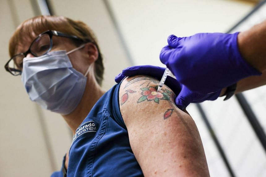 A nurse receives a dose of the Pfizer-BioNTech vaccine in Aurora, Colorado.