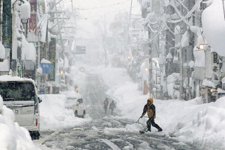 People remove snow on a street in Yuzawa, Niigata Prefecture, on Dec 17, 2020.