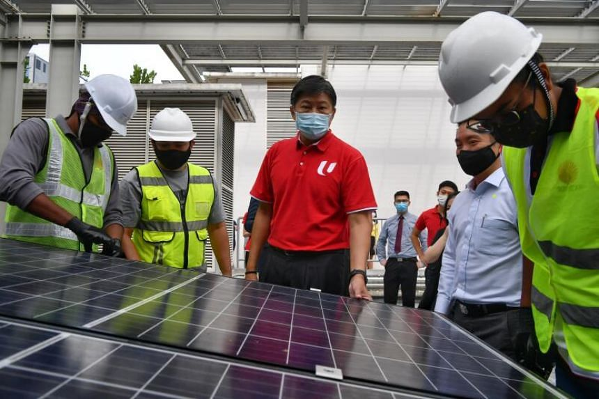 NTUC's Secretary-General Ng Chee Meng (centre) observes workers as they install a solar panel during the Career Development Plan for the Solar Industry event on Dec 17, 2020.