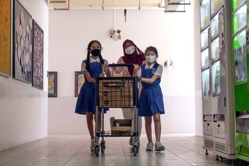 Ms Nur Ilyana Mohamed Anwar (centre) roped in her pupils at CHIJ Our Lady of the Nativity to help pack the Hearts of Hope art kits that were distributed as part of Children's Day celebrations.