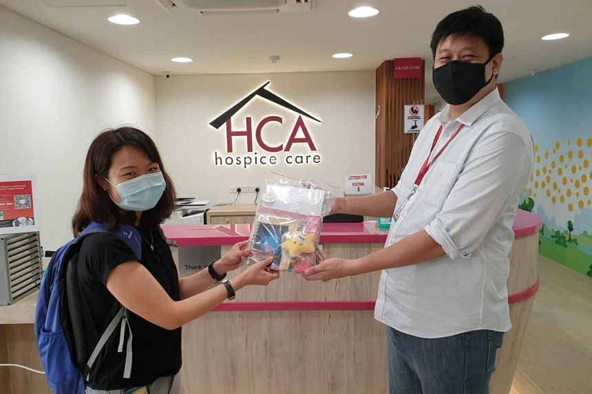 A Light in the Night founder Florence Fong passing one of her care packs to a representative from HCA Hospice Care.
