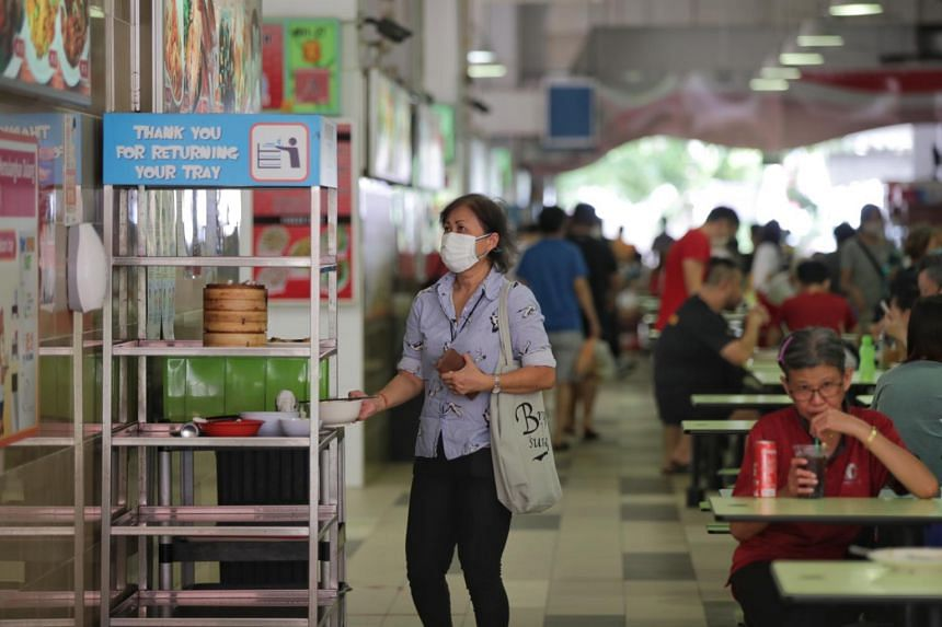 A woman taking a used bowl to the return station at a hawker centre on Aug 10, 2020.