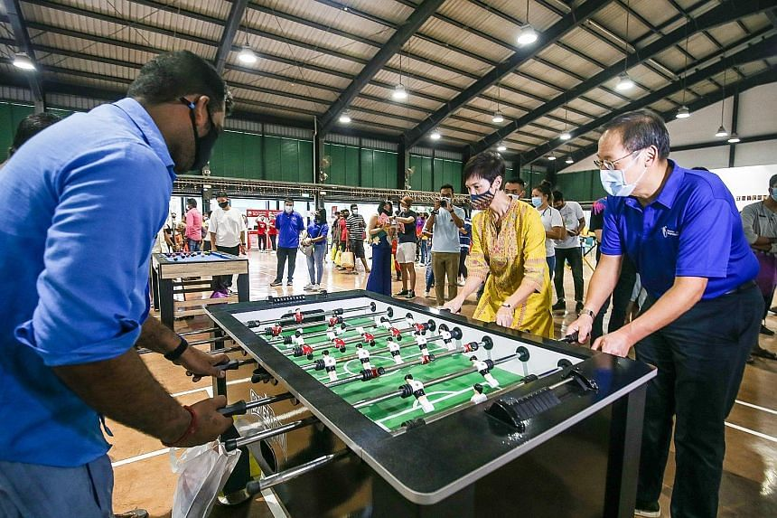 Manpower Minister Josephine Teo and Second Minister for Manpower Tan See Leng playing table football with a migrant worker at Terusan Recreation Centre in Jurong yesterday.