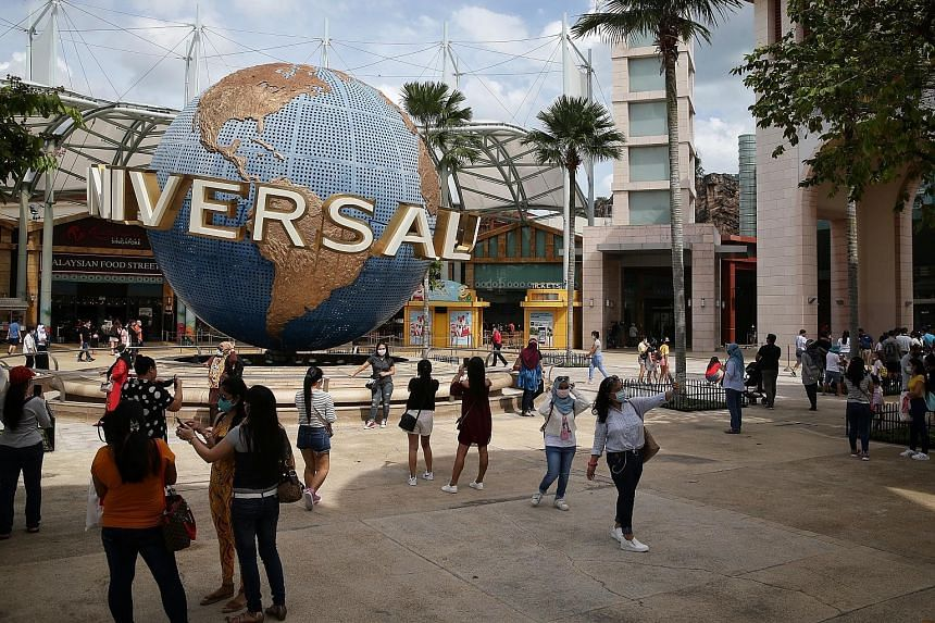Visitors taking photos in front of Universal Studios Singapore in Sentosa earlier this month. Three in 10 respondents to the Sunday Times survey said they are likely to use the vouchers on attraction tickets, while almost two in 10 said they would go