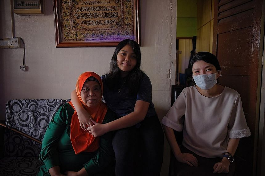 Mayflower Primary School pupil Nurul Netrisya with her grandmother Saengmai and Kampung Kaki volunteer Tracy Bay at Madam Saengmai's Ang Mo Kio flat. Ms Bay, a civil servant, helped Nurul with her schoolwork, guiding her through her weaker subjects.