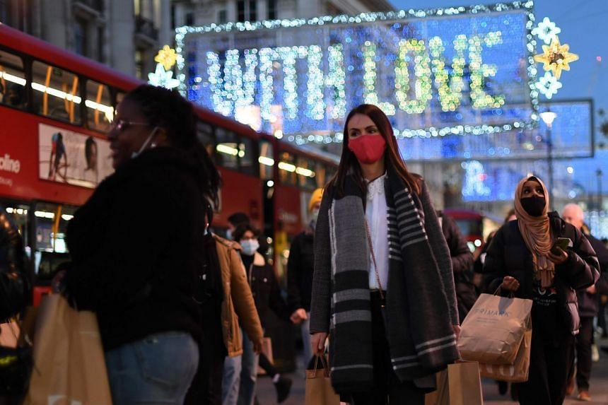 Shoppers walk along Regent Street, in the main high-street shopping area of London, on Dec 15, 2020.
