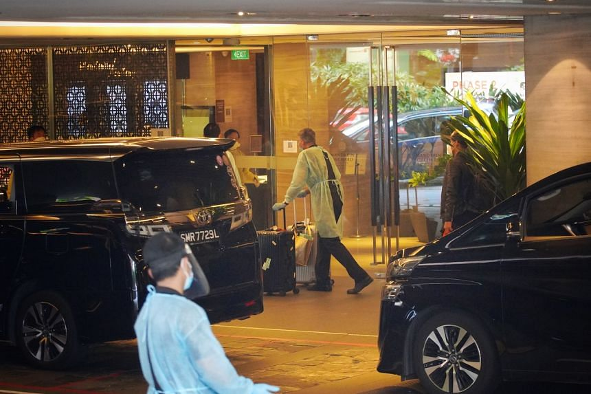 Staff in PPE helping to move luggage as guests leave the Mandarin Orchard hotel on Dec 20, 2020.