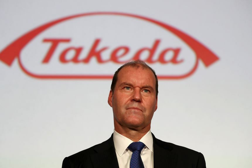 Takeda chief executive Christophe Weber stands before a company logo after a press conference in Tokyo.