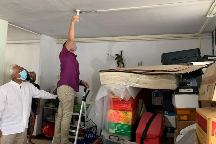 Minister Maliki Osman helping to install a bulb at a resident's home, on Dec 20, 2020.