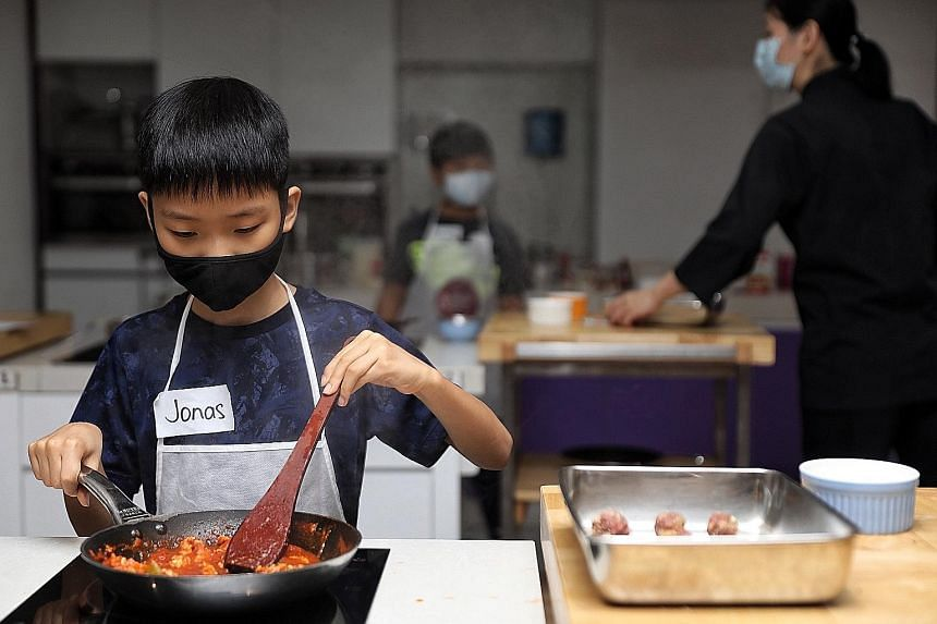 Jonas Ang (above), eight, cooks chicken for a cottage pie at ToTT at Century Square. A Christmas log cake-making class at Creative Culinaire The School. A baked mac and cheese class at Little Bakers' Lab (above).