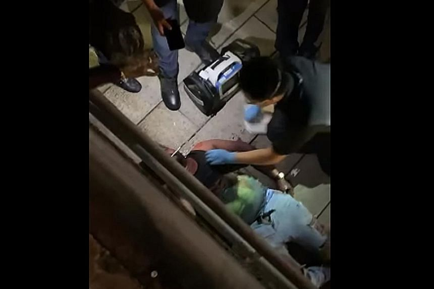 A screengrab of a video of the fight, which shows paramedics tending to a man lying on a walkway leading towards an underpass outside The Central mall in Clarke Quay on Saturday night.