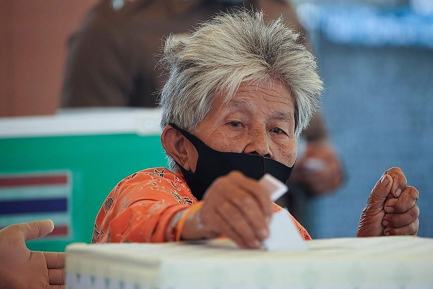 A woman casting her vote at a polling station in Prachuap Khiri Khan province yesterday. Polling officials reported a steady voter turnout. PHOTO: REUTERS People looking for their names on voter lists at a polling station in Prachuap Khiri Khan provi