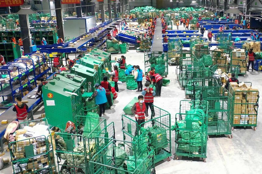 Workers sort packages for delivery at a warehouse of China Post Group in Hengyang, China, on Nov 12, 2020.