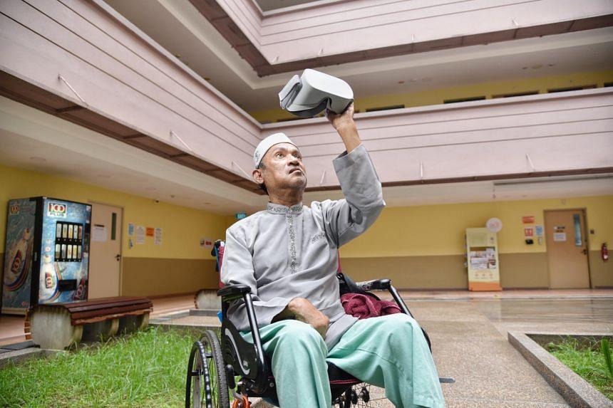 Mr Abdul Rahim Abdullah holding the virtual reality headset at Jamiyah Nursing Home, on Dec 16, 2020.