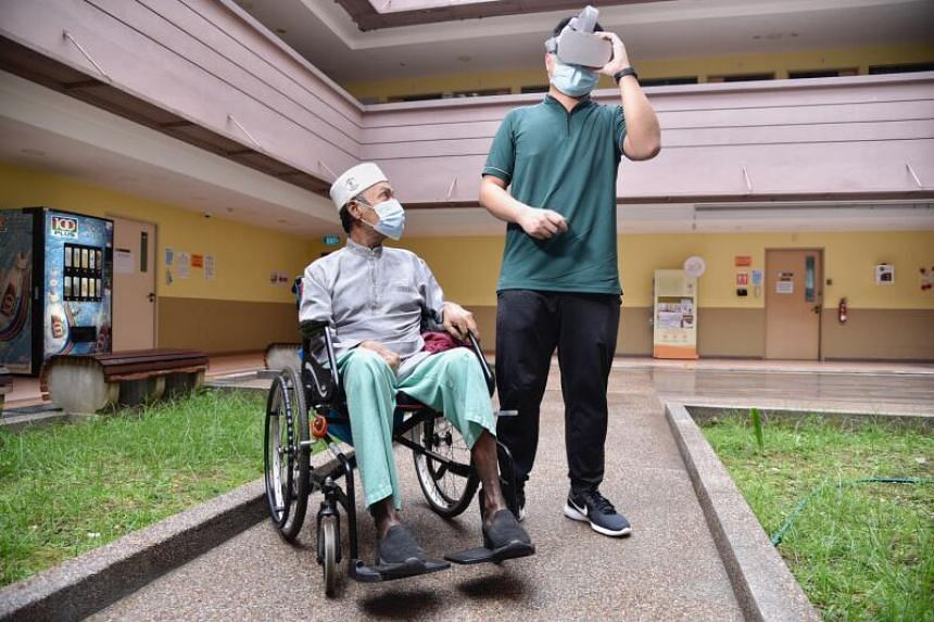 Therapy assistant Mark Kevin Bartolome holding the VR headset for Mr Abdul Rahim Abdullah at Jamiyah Nursing Home, on Dec 16, 2020.