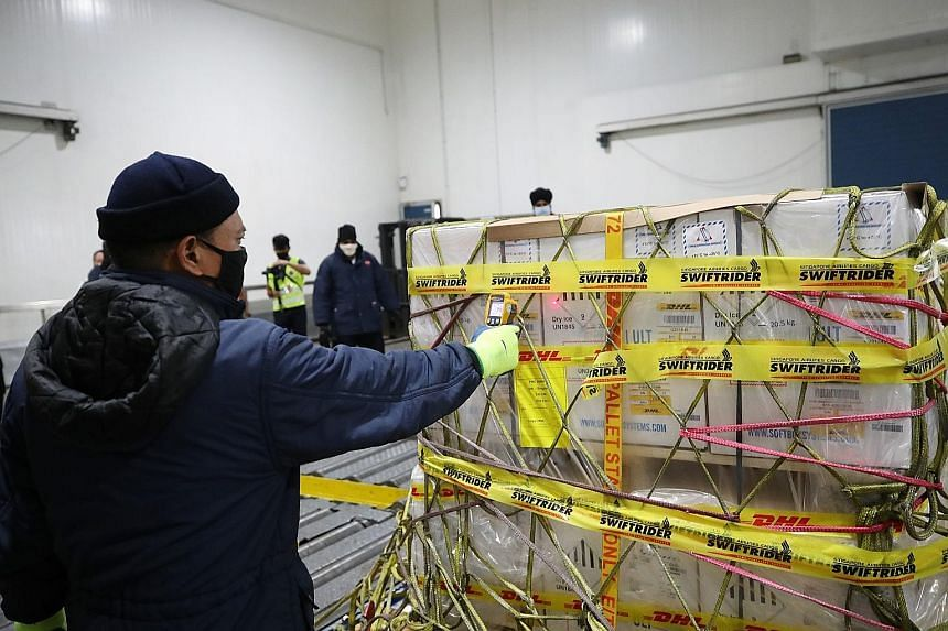 Left: The Covid-19 vaccines arriving at a cold chain management facility run by cargo handler Sats at Changi Airport. Above: The vaccines will be placed in a storage facility with capabilities of handling ultra-cold storage at about minus 80 deg C. T