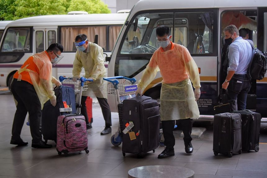 Attendants at Changi Airport's Terminal 3 handling luggage belonging to passengers from a flight which arrived from London on Dec 22,, 2020.