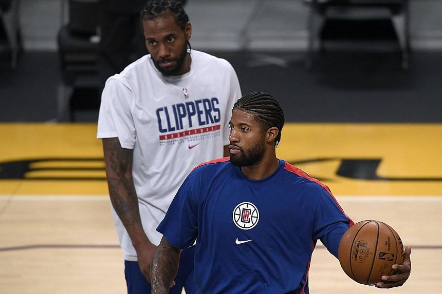 Clippers duo Paul George and Kawhi Leonard (background) during pre-season, which they finished 0-3. George knows the off-season and their season opener against the Lakers will not define their campaign. Below: Lakers stars Anthony Davis and LeBron Ja