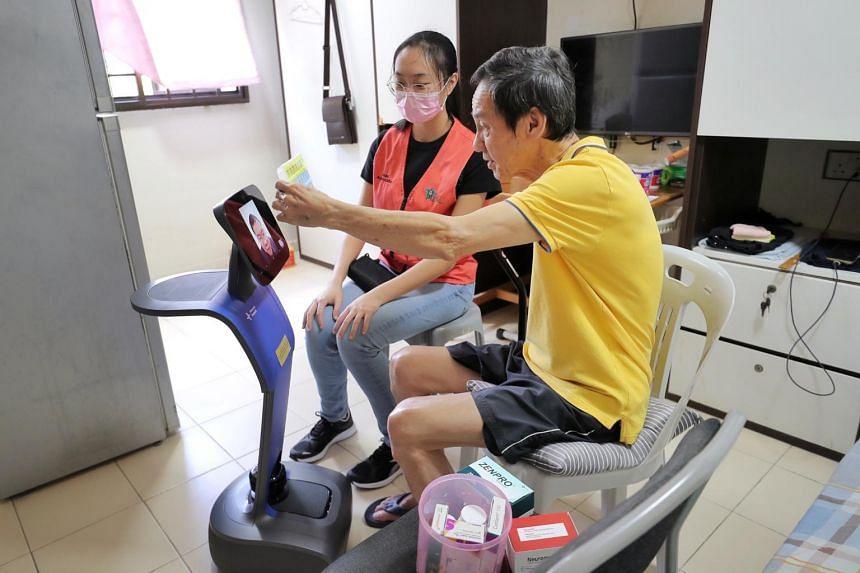 Mr Ow Soo Tian speaking to pharmacist Joshua Low via Alexandra Hospital's robot Temi.