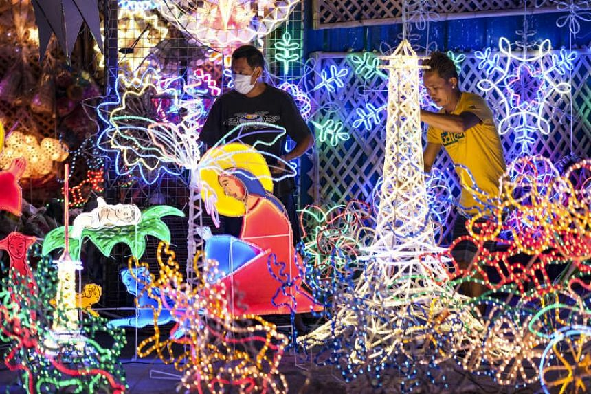 Customers look at illuminated festive decorations at a store in San Fernando, Pampanga, Philippines on Dec 17, 2020.