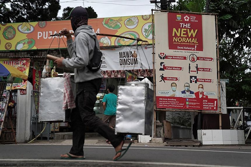 A vendor walking past a sign about Covid-19 prevention measures in Bandung, West Java, earlier this month. Indonesia's Phase 3 clinical trial of Sinovac Biotech's CoronaVac was poorly organised and failed to gather the data for the vaccine to be appr