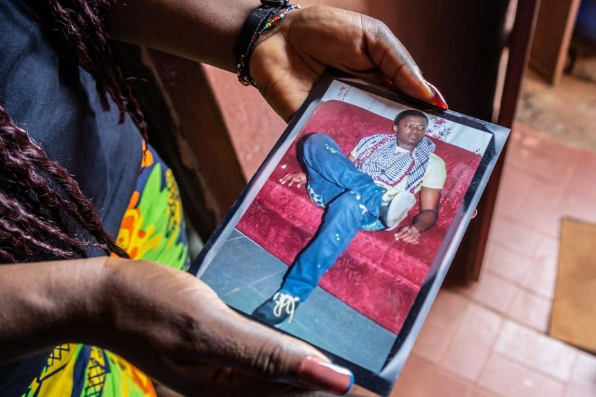 Hope Iloanya holds a photo of her son Chijioke Iloanya, whom she last saw in 2012 when he disappeared at age 20 after being in police custody.