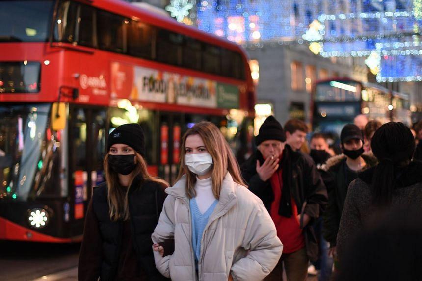Shoppers walk along Regent Street in the main high-street shopping area of London on Dec 15, 2020.