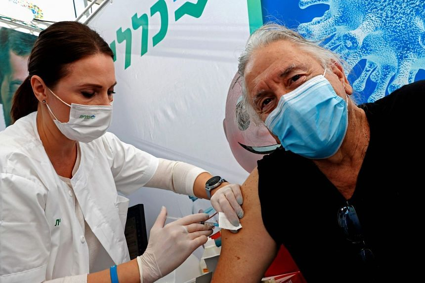 A senior looks away as he gets vaccinated against Covid-19 in Tel Aviv,on Dec 23, 2020.