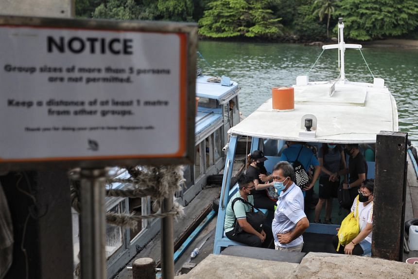 Visitors leaving Pulau Ubin for Changi Point Ferry Terminal. In the foreground is a sign from the National Parks Board reminding visitors to adhere to safe distancing measures.