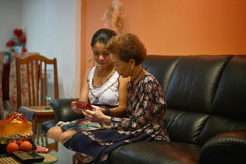 Dr Skye Yeo with her mother, Madam Julie Yen, 77, tinkering with an MP3 radio that will be used for Project Audible Cheer on Tuesday. About 700 of such radio sets have been given out since April.