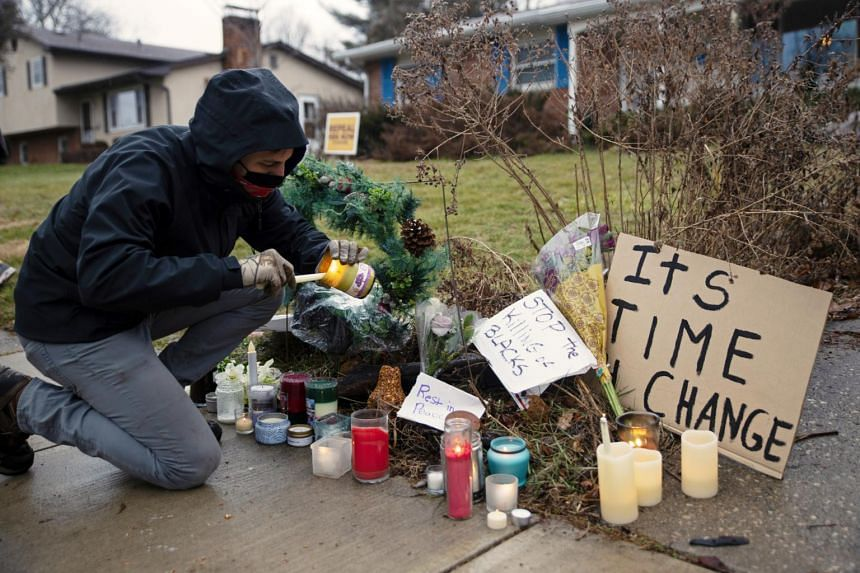 A protester lights a candle outside the home where Andre Maurice Hill was killed in Columbus, Ohio, on Dec 24, 2020.