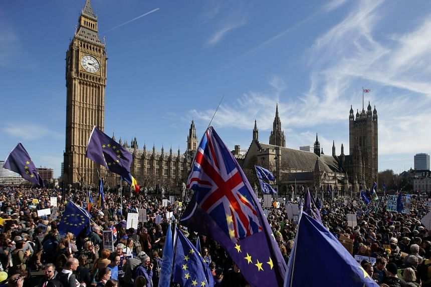 A 2017 photo shows demonstrators holding EU and Union flags gathered in front of the Houses of Parliament in London.
