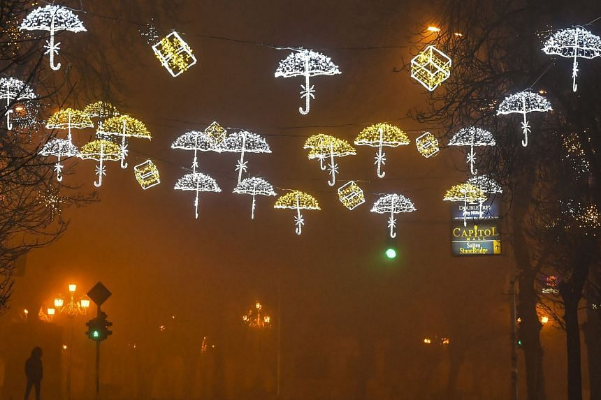 A man walking through an empty, decorated street during heavy fog and air pollution that covered Skopje valley in Skopje, the Republic of North Macedonia, yesterday. Fog, smog, increased emissions on account of household heating requirements and othe