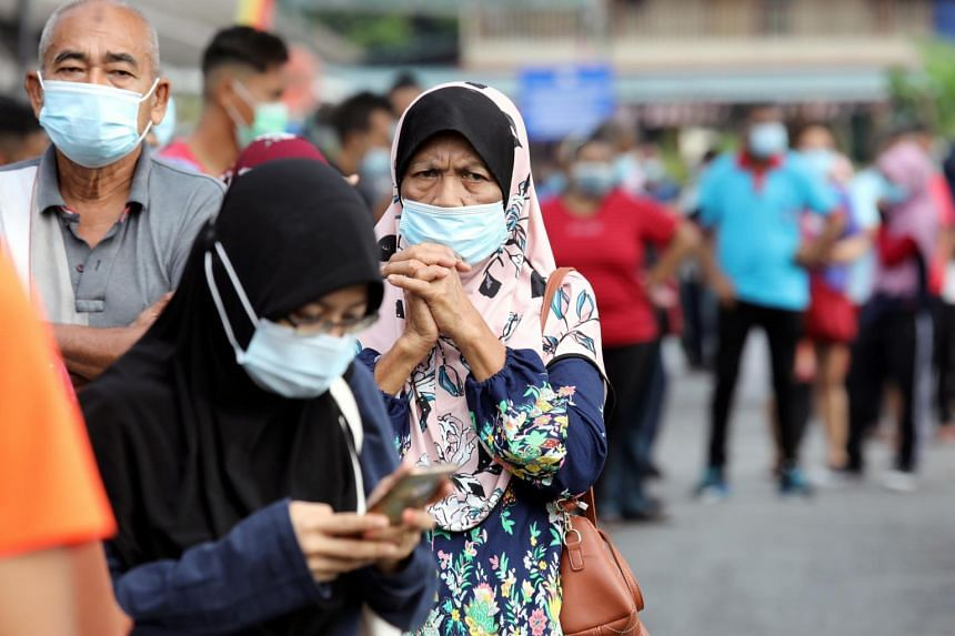 People wait in line to be tested at a station in Klang, Malaysia on Dec 2, 2020.