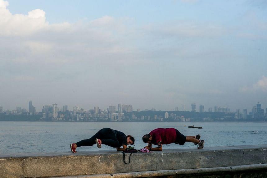 People do yoga at the Marine Drive waterfront in Mumbai on Sept 30, 2020.