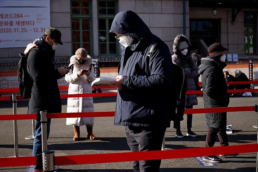 People queueing on Friday at a temporary coronavirus testing site in front of a railway station in Seoul. South Korea posted its second-highest daily number of cases yesterday. The government plans to meet today to discuss whether to tighten distanci
