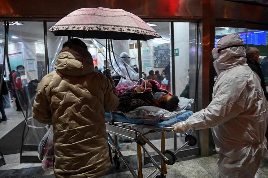 Medical staff members arrive with a patient at the Wuhan Red Cross Hospital in Wuhan on Jan 25, 2020.